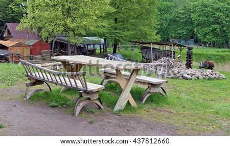 Recreation area on a farm - a wooden table and a bench for a barbecue. On the back plan - a shed and a heap of granite cobble-stones - stock photo