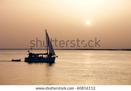 Recreation boat at sunset, in Ria Formosa, natural conservation region in Algarve, Portugal. - stock photo