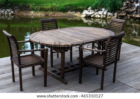 Recreation concept. Wooden table and cheers in summer garden. Relaxation zone near the lake