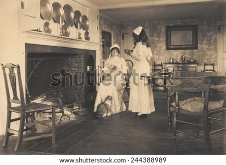Recreation Of A Gentile Colonial American House With Two Women In Colonial  Costume. 1913 Photo