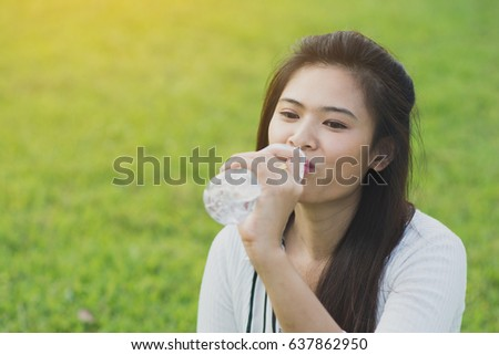 Recreation of young woman with drinking water on nature, park, forest.