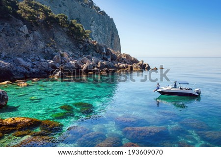 Recreation on the boat near the shore of a beautiful mountain. Couple traveling on the sea near the island. - stock photo