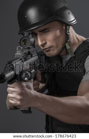 Recreation, paintball sport player wearing protective helmet aiming pistol ,black armor and machine gun