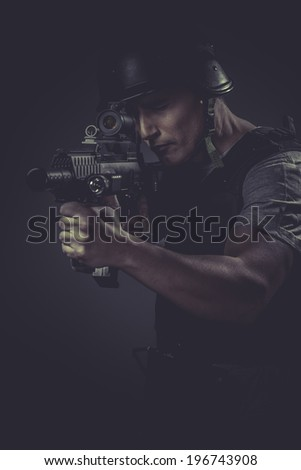 recreation player wearing protective helmet aiming pistol ,black armor and machine gun - stock photo