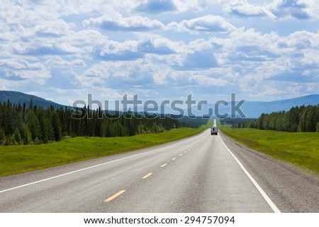 Recreational Vehicle RV southbound on empty road of Alaska Highway, Alcan, in boreal forest taiga landscape south of Fort Nelson, British Columbia, Canada