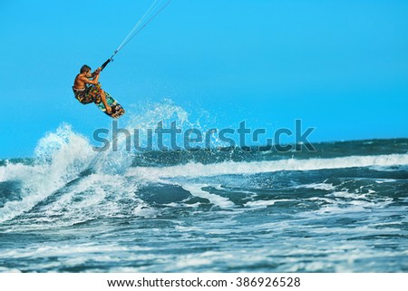 Recreational Water Sports Action. Healthy Man ( Surfer ) Kiteboarding ( Kite Surfing ) On Waves In Sea, Ocean. Extreme Sport. Summer Fun, Vacation. Active Lifestyle. Leisure Sporting Activity. Hobby - stock photo