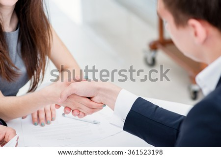 Recruitment. Business woman and businessman shaking hands in the office in formal attire. - stock photo