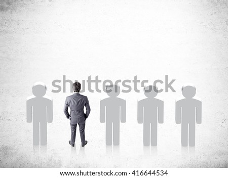 Recruitment concept with businessman and people icons on concrete background - stock photo