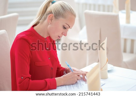 Recruitment. Confident young businessman in full suit fills the paper sitting at the desk in the office