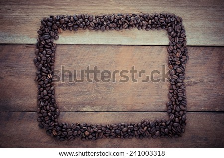 Rectangle frame made of coffee beans on the wooden background - stock photo
