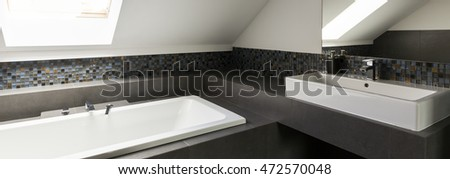 Rectangular bathtub and sink in well lighted bathroom
