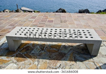 Rectangular cement bench with square holes on the stone pavement by the calm sea - stock photo