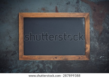 Rectangular chalkboard with copy space isolated on dark metal background - stock photo