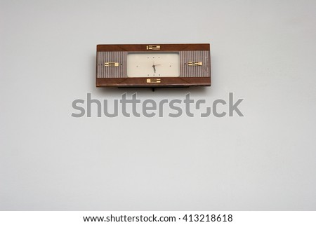 Rectangular clock hanging on a white wall - stock photo
