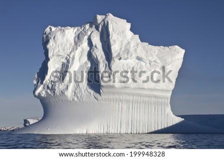 rectangular iceberg sunny summer day in Antarctic waters - stock photo