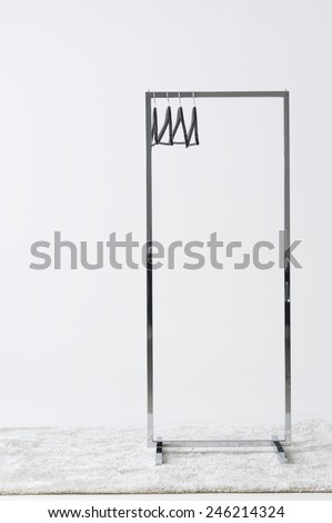 Rectangular metal clothing rail with empty coat hangers standing on a white carpet against an off white wall with copyspace - stock photo