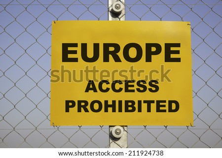 rectangular yellow danger sign at a metal border chain-link fence in front of a blue sky. The caution label is warning about Europe, access prohibited. Concept for undesirable immigration. - stock photo