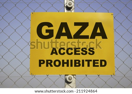 rectangular yellow danger sign at a metal chain-link border fence in front of a blue sky. The caution label is warning about Gaza, access prohibited. Concept for Israel Palestine conflict.  - stock photo