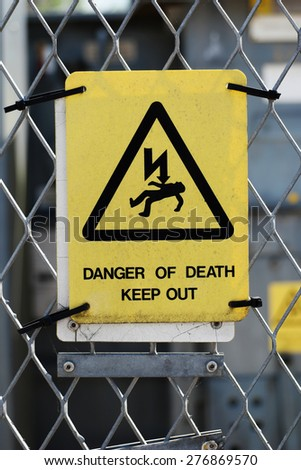 Rectangular yellow high voltage warning sign warning of the risk of death mounted on a wire mesh perimeter fence - stock photo