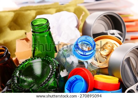 Recyclable garbage consisting of glass, plastic, metal and paper isolated on white background - stock photo