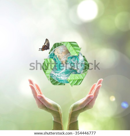 Recycle arrow sign leaf around green globe over beautiful woman human hands on blurred abstract greenery bokeh background: Recycle reduce reuse CSR idea concept: Element of the image furnished by NASA