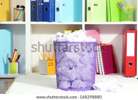 Recycle bin filled with crumpled papers, on floor in office room - stock photo