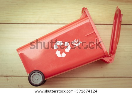 recycle bin trash bin with recycle logo on wood background vintage color tone. - stock photo