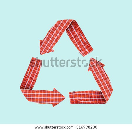 Recycle Logo from used shirt fabric on light blue background - stock photo