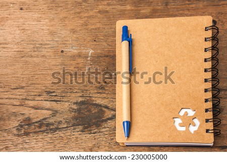 recycle notebook and pen on wooden background,vintage color tone.