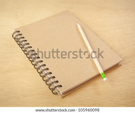 recycle notebook and wooden pencil on wood background - stock photo