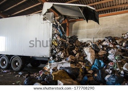 Recycle plant. truck unloading huge amounts of garbage, recycle plant in spain - stock photo