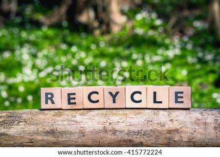 Recycle sign in a green forest in the spring - stock photo