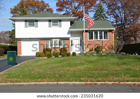 Recycle trash container American flag pole Recycle trash container driveway of Suburban Brick High Ranch home autumn day residential neighborhood clear blue sky USA - stock photo