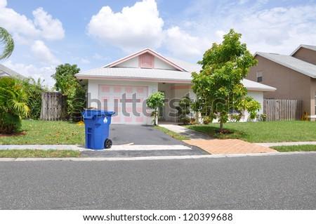 Recycle Trash Container Curb of Suburban Ranch Bungalow Home Sunny Blue Sky Day Clouds - stock photo