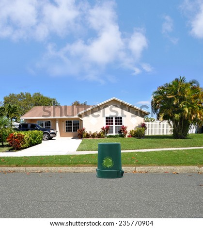 Recycle trash container suburban ranch style home sunny residential neighborhood blue sky clouds USA