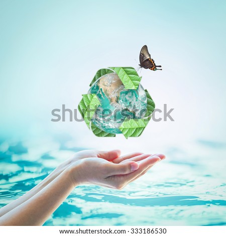 Recycled arrow sign leaf around green globe w/ butterfly over beautiful women human hands on blurred abstract natural water background: CSR eco sea concept: Element of this image furnished by NASA    - stock photo