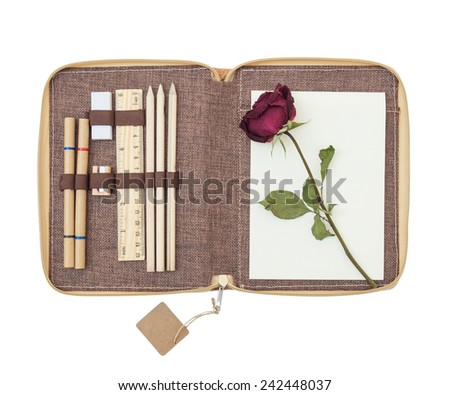 Recycled notebook with stationery and dried roses isolated on white background