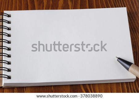 Recycled paper notebook and recycled paper pen on wooden table.