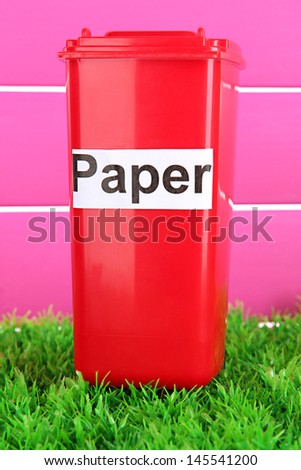 Recycling bin on grass on pink background
