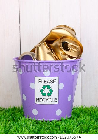 Recycling bin on green grass near wooden fence - stock photo