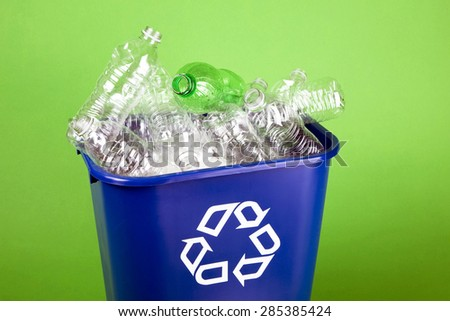 Recycling bin overflowing with empty plastic water bottles. - stock photo