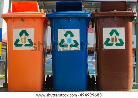 Recycling bins in Malaysia. Orange bin is for plastic and aluminium cans, Blue bin for paper, and Brown bin for glass