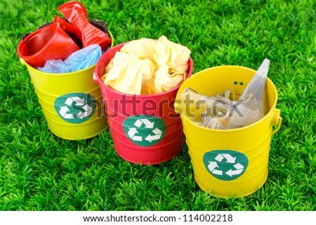 Recycling bins on green grass - stock photo