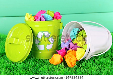Recycling bins on green grass on color wooden background - stock photo