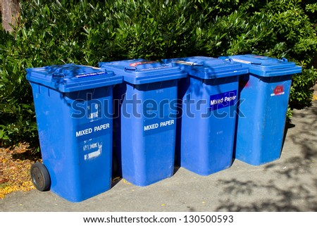 Recycling bins upright with natural background