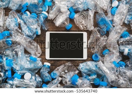 Recycling concept. Tablet wooden background around the transparent plastic bottles. The problem of ecology, environmental pollution.