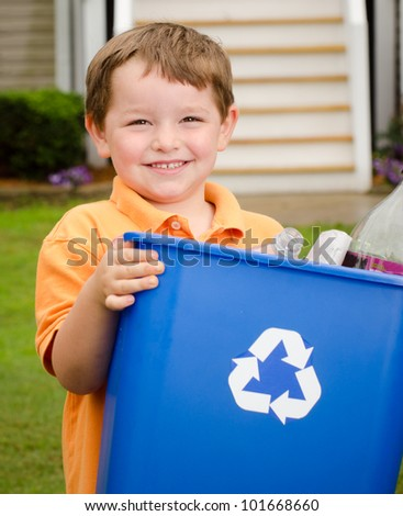 Recycling concept with young child carrying recycling bin to the curb at his house - stock photo