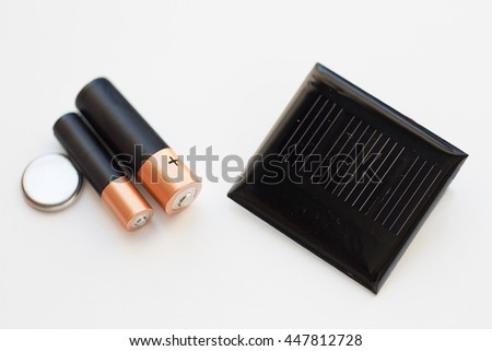 recycling, energy, power, environment and ecology concept - close up of alkaline batteries and solar cell - stock photo