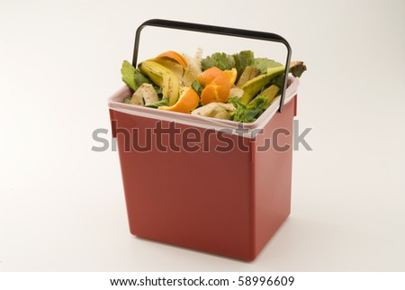 Recycling food waste for compost in a red bin. White background.