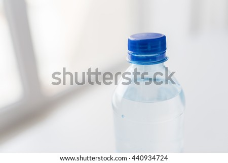 recycling, healthy eating and food storage concept - close up of plastic bottle with pure drinking water on table - stock photo